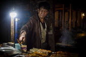 A worker cooking street food. Dali, China. - Connor Matheson - Chinese,2010s,2015,at,china,cities,City,cook,COOKERY,cooking,cooks,EARNINGS,EBF,Economic,Economy,employee,employees,Employment,EQUALITY,food,FOODS,Income,INCOMES,inequality,job,jobs,kebab,kebabs,LBR,L