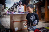 Young people selling handmade jewellery to wealthy Chinese tourists. Lijiang, Yunnan Province, China. - Connor Matheson - ,2010s,2015,AFFLUENCE,AFFLUENT,Bourgeoisie,boy,boys,buy,buyer,buyers,buying,child,CHILDHOOD,children,china,Chinese,commodities,commodity,EARNINGS,EBF,Economic,Economy,elite,elitism,employee,employees,