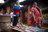 Young people selling handmade jewellery to wealthy Chinese tourists. Lijiang, Yunnan Province, China. - Connor Matheson - 2010s,2015,AFFLUENCE,AFFLUENT,Bourgeoisie,buy,buyer,buyers,buying,china,Chinese,commodities,commodity,EARNINGS,EBF,Economic,Economy,elite,elitism,employee,employees,Employment,EQUALITY,goods,handmade,