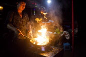 A worker cooking street food. Kunming, Yunnan Province, China. - Connor Matheson - 26-09-2015