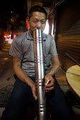 A man smoking a cigerette through a bong. Dongchuan, Yunnan Province, China. - Connor Matheson - Chinese,2010s,2015,at,china,cigarette,cigarettes,cities,City,enjoy,enjoying,enjoyment,Leisure,LFL,LIFE,male,man,men,nicotine,night,night at night,Night Out,night time,nightlife,PEOPLE,person,persons,R