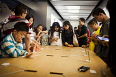 Wealthy Chinese tourists looking at the Iphone. Apple Store, Nanjing Road, Shanghai, China. - Connor Matheson - ,2010s,2015,adolescence,adolescent,adolescents,AFFLUENCE,AFFLUENT,Apple Inc,bought,Bourgeoisie,boy,boy boys,boys,busy,buy,buyer,buyers,buying,CELLULAR,child,child children,CHILDHOOD,children,china,Chi