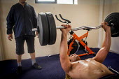 Syrian refugee weight lifting in the communal gym, Marsa Open Centre, Malta. - Connor Matheson - 14-07-2015
