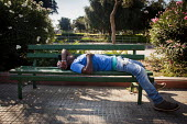 A man rests after working during the morning, bus stop for the Hal Far Refugee Camp. Valletta, Malta. - Connor Matheson - 2010s,2015,African Africans,asleep,BAME,BAMEs,bench,Black,BME,bmes,bus,bus service,BUSES,camp,camps,Diaspora,displaced,diversity,ethnic,ethnicity,eu,european,europeans,eurozone,exhausted,EXHAUSTION,fo
