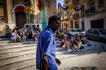 Malta, Mahjoub a Sudanese refugee walking past tourists visiting Malta. Msida, Malta. - Connor Matheson - 2010s,2015,African Africans,BAME,BAMEs,Black,BME,bmes,Diaspora,displaced,diversity,ethnic,ethnicity,eu,european,europeans,eurozone,foreign,foreigner,foreigners,holiday,holiday maker,holiday makers,hol