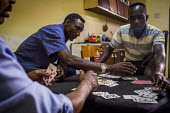 Malta, Mahjoub, a Sudanese refugee playing cards with his friends who are also refugees from Sudan. Valletta, Malta. - Connor Matheson - 20-07-2015