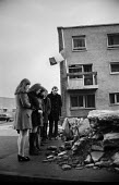 Bloody Sunday, Derry 1972. Local residents stand in respectful silence at a makeshift shrine for one of the Derry 13 killed by British paratroopers, as an Irish tricolor flag flies at half mast - Martin Mayer - 1970s,1972,Armed Forces,army,Bloody,Bloody Sunday,British Army,British troops,Catholic,Catholics,child,CHILDHOOD,children,Civil Rights,communities,community,conflict,Conflicts,cross,death,deaths,Derry
