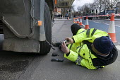 Trucks pulled over as part of the regular roadside checks by DVSA staff to ensure that HGVs are safe to drive on British roads. A vehicle inspector with many years experience inspects worn tyres on an... - Stefano Cagnoni - 2010s,2015,camera,cameras,check,check checking,checking,cities,city,CLJ,DVSA,employee,employees,Employment,enforcement,evidence,examiner,examiners,examining,HAULAGE,HAULIER,HAULIERS,HGV,HGVs,high visi