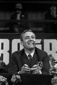 Tony Benn smoking his pipe, Labour Party Conference 1968 - NLA - 1960s,1968,Conference,conferences,EMOTION,EMOTIONAL,EMOTIONS,funny,Humor,HUMOROUS,HUMOUR,joking,Labour Party,Labour Party Conference,LAUGH,laughing,LAUGHTER,lighting,male,man,men,MP,MPs,Party,people,p