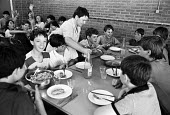 Miners children on a summer holiday in France during the Miners Strike 1984, hosted by French trade union members in solidarity. Children being served food and drink donated by the CGT, the CGT Mineur... - Stefano Cagnoni - 1980s,1984,boy,boys,canteen,CANTEENS,CGT,child,CHILDHOOD,children,dining,dinner,dinners,disputes,Europe,feed,feeding,FEMALE,food,FOODS,France,french,holiday,holidays,INDUSTRIAL DISPUTE,juvenile,juveni