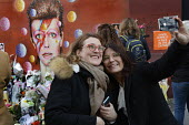 Two young women take a selfie infront of the David Bowie Memorial Wall, Brixton, London - Janina Struk - 2010s,2016,ACE,Arts,Bowie,CAMERA,cameras,cities,city,Culture,David Bowie,dead,death,deaths,died,FEMALE,floral tribute,floral tributes,flower,flowering,flowers,iphone,London,melody,memorial,memories,me