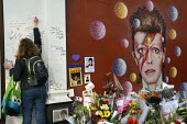 Woman writing a a message of condolences on the David Bowie Memorial Wall, Brixton, London - Janina Struk - 2010s,2016,ACE,Arts,cities,city,commemorate,COMMEMORATING,commemoration,COMMEMORATIONS,condolence,condolences,Culture,David Bowie,dead,death,deaths,died,FEMALE,floral tribute,floral tributes,flower,fl