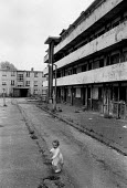 A child playing in the street, London docklands 1982 - John Harris - 1980s,1982,child,CHILDHOOD,children,cities,City,EQUALITY,eu,european,europeans,europeregi,excluded,exclusion,female,females,flat,flats,girl,girls,HARDSHIP,Housing Estate,impoverished,impoverishment,IN
