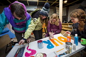 Teachers from the UK volunteer to teach refugees over half term campaign to Save Our School, The Jungle camp, Calais, France. Painting a banner - Jess Hurd - 19-02-2016
