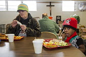 Flint, Michigan, young girl eating, North End Soup Kitchen. The soup kitchen is operated by Catholic Charities - Jim West - &,2010s,2016,African American,African Americans,African-American,America,assistance,BAME,BAMEs,Belief,black,BME,bmes,Catholic,Catholic Charities,catholicism,Catholics,charitable,charity,child,CHILDHOO