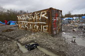 Squalid conditions in the Grande-Synthe refugee camp. Dunkirk, France. Graffiti You will never walk alone on a shippiung container - Jess Hurd - 2010s,2016,alone,BAME,BAMEs,Black,BME,bmes,Calais,camp,camps,Diaspora,dirty,displaced,diversity,ethnic,ethnicity,eu,Europe,european,europeans,europeregi,eurozone,foreign,foreigner,foreigners,France,fr