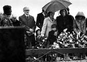 Funeral of the IRA prisoner Bobby Sands, 1981, Sister Marcella (in black), mother Rosaleen and son Gerald of Bobby Sands pay respects at his funeral, Milltown Cemetery, Belfast, Northern Ireland - Katalin Arkell - 1980s,1981,adult,adults,Belfast,Bobby Sands,casket,catholic,catholics,cemeteries,Cemetery,cities,city,coffin,conflict,DEATH,DEATHS,died,disputes,europeregi,families,FAMILY,FEMALE,floral,flower,floweri