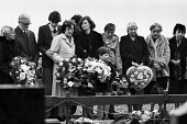 Funeral of the IRA prisoner Bobby Sands, 1981, Sister Marcella (in black), mother Rosaleen and son Gerald pay respects at his funeral, Milltown Cemetery, Belfast, Northern Ireland - Katalin Arkell - 1980s,1981,adult,adults,Belfast,Bobby Sands,casket,catholic,catholics,cemeteries,Cemetery,cities,city,coffin,conflict,DEATH,DEATHS,died,disputes,europeregi,families,FAMILY,FEMALE,floral,flower,floweri