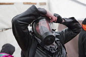 Jason N. Parkinson, video journalist putting on a gas mask. Demolition of the Jungle refugee camp, Calais, France - Jess Hurd - 03-03-2016
