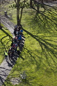 School group of teachers and children walking through a park on a sunny winters day. Tower Hamlets, East London. - Jess Hurd - 2010s,2016,BME black,child,CHILDHOOD,children,cities,City,class,East London,EDU,educate,educating,Education,educational,ethnic,ETHNICITY,grass,Green,green space,ISLAM,ISLAMIC,juvenile,juveniles,kid,ki
