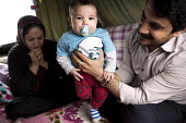 Amir, his wife, Maryam and daughter Rosie (3 months), Kurdish refugees in the makeshift Jungle camp Calais, France. - Jess Hurd - 2010s,2016,adult,adults,authorities,babies,baby,BME black,Calais,camp,camps,caravan,caravans,child,CHILDHOOD,children,DAD,DADDIES,DADDY,DADS,Diaspora,displaced,EARLY YEARS,ethnic,ETHNICITY,eu,Europe,e