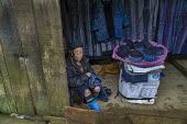 Hmong woman selling traditional indigo dyed clothing from a stall, Sapa mountains, Vietnam - David Bacon - SUBSISTENCE,2010s,2015,age,ageing population,apparel,artisan,Asia,asian,asians,asiaregi,BAME,BAMEs,BME,bmes,Business,cloth,clothes,clothing,costume,craft,cultivation,diversity,EARNINGS,EBF,Economic,Ec