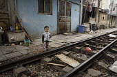 Homes next to the railway tracks, Hanoi, Vietnam - David Bacon - 2010s,2015,Asia,asian,asians,asiaregi,boy,boys,child,CHILDHOOD,children,EARLY YEARS,EQUALITY,excluded,exclusion,Hanoi,HARDSHIP,home,Homes,house,houses,Housing,impoverished,impoverishment,INEQUALITY,in