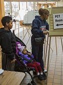 Detroit, Michigan Children watching mother voting in the primary presidential election - Jim West - ,2010s,2016,adult,adults,African American,African Americans,African-American,America,ballot,BALLOTING,ballots,BAME,BAMEs,black,BME,bmes,booths,boy,boys,child,CHILDHOOD,children,democracy,Detroit,diver