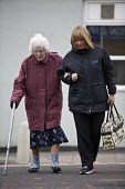 Carer helping an elderly woman cross the road, Easington Lane, Hetton, Tyne and Wear - John Harris - 2010s,2016,adult,adults,age,ageing population,assistant,assistants,assisting,bought,buy,buyer,buyers,buying,care,Care Worker,care workers,carer,carers,caring,charitable,charity,commodities,commodity,c