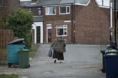 Woman struggling up the hill, Easington Lane, Hetton, Tyne and Wear - John Harris - 2010s,2016,bag,bags,bought,buy,buyer,buyers,buying,commodities,commodity,consumer,consumers,customer,customers,disabilities,disability,disable,disabled,disablement,EQUALITY,excluded,exclusion,fat,FEMA