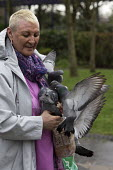 Woman feeding the birds, Port Talbot, South Wales - John Harris - 2010s,2016,adult,adults,AGE,ageing population,animal,animals,bird,birds,ELDERLY,feed,feeding,feeds,FEMALE,feral pigeon,feral pigeons,Leisure,LFL,LIFE,MATURE,OAP,OAPS,OLD,older,pensioner,pensioners,PEO