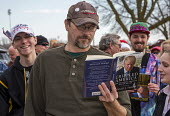 Wisconsin, supporter reading Crippled America, How to make America Great Again by Donald Trump, queuing for Republican presidential nomination campaign rally - Jim West - 03-04-2016