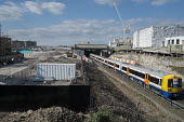 Overground train and controversial Earls Court development site, London. - Philip Wolmuth - passenger, passengers, property development, public transport, railway, railways, redevelopment, regeneration, train, trains, urban,2010s,2016,brownfield site,building,BUILDINGS,carriage,carriages,cit