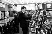 Men gambling slot machines and playing pinball, Amusement Arcade, Soho, London, 1968 - Romano Cagnoni - 1960s,1968,amusement arcade,amusement arcades,bet,bets,betting,change,cities,city,coin,Coinage,coins,gamble,gambler,gamblers,gambling,Leisure,LFL,LIFE,London,machine,MACHINERY,machines,male,man,mechan