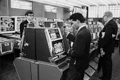 Men gambling on slot machines, Amusement Arcade, Soho, London, 1968 - Romano Cagnoni - 1960s,1968,amusement arcade,amusement arcades,bet,bets,betting,change,cities,city,coin,Coinage,coins,gamble,gambler,gamblers,gambling,Leisure,LFL,LIFE,London,machine,MACHINERY,machines,male,man,mechan