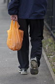 Shopper walking with a plastic bag - John Harris - 2010s,2016,age,ageing population,bag,bags,bought,buy,buyer,buyers,buying,commodities,commodity,consumer,consumers,customer,customers,elderly,EQUALITY,excluded,exclusion,goods,HARDSHIP,impoverished,imp