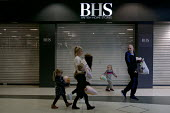 Family walking past closed shutters. Closing BHS Store Telford Shopping Centre Shropshire. 11,000 jobs go as Retail Acquisitions put the department store into administration - John Harris - 2010s,2016,administration,adult,adults,apparel,bag,bags,bankrupt,bankruptcy,bought,buy,buyer,buyers,buying,child,CHILDHOOD,children,cities,City,closed,closed down,closing,closure,closures,clothes,clot