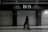 Shopper walking past closed shutters.Closing BHS Store Telford Shopping Centre Shropshire. 11,000 jobs go as Retail Acquisitions put the department store into administration - John Harris - 2010s,2016,administration,apparel,Asian,Asians,BAME,BAMEs,bankrupt,bankruptcy,Black,BME,bmes,bought,buy,buyer,buyers,buying,cities,City,closed,closed down,closing,closure,closures,clothes,clothing,com