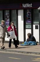 Elderly shoppers walk past a beggar outside NatWest bank, Stratford-upon-Avon, Warwickshire - John Harris - 25-04-2016