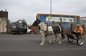 Man driving a horse and trap past a flat bed truck full of scrap metal queuing to enter a scrapyard, Willenhall, Wolverhampton - John Harris - 06-05-2016