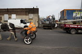 Man driving a horse and trap past a flat bed truck full of scrap metal queuing to enter a scrapyard, Willenhall, Wolverhampton - John Harris - ,2010s,2016,animal,animals,BAME,BAMEs,BME,bmes,cart,CCRS,cities,City,cob,cobs,diversity,domesticated ungulate,domesticated ungulates,driver,drivers,driving,EBF,Economic,Economy,equestrian,equine,ethni