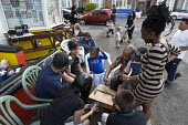 Street party at a corner shop, Coventry, playing draughts - John Harris - 2010s,2016,Asian,Asians,BAME,BAMEs,black,BME,bmes,boy,boys,child,CHILDHOOD,children,cities,City,communities,community,Corner Shop,Coventry,cultural,diversity,EMOTION,EMOTIONAL,EMOTIONS,EQUALITY,ethnic