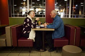 An elderly couple enjoy a McDonalds meal, Sheffield, Yorkshire - Connor Matheson - 2010s,2016,adult,adults,age,ageing population,beef burger,beef burgers,beefburger,beefburgers,burger,burgers,catering,cities,City,communicating,communication,conversation,conversations,couple,COUPLES,