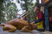 Hanoi, Vietnam, A small shop selling dog meat on the street - David Bacon - 2010s,2015,animal,animals,Asia,asian,asians,asiaregi,canine,chef,chefs,cook,COOKERY,cooking,COOKS,dog,dog meat,dogs,eat,EBF,Economic,Economy,employee,employees,Employment,FEMALE,food,FOODS,gastronomy,