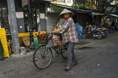 Streetseller selling tangerines from a bicycle on the street, Hanoi, Vietnam - David Bacon - 09-12-2015