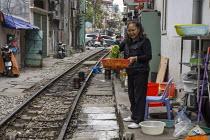 Homes next to the railway line, Hanoi, Vietnam. Woman preparing food, washing salad leaves - David Bacon - 09-12-2015