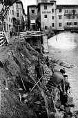 Florence Floods, Italy, 1966 in which 100 died and many cultural artefacts, books, paintings and sculptures were damaged. It was the worst flood for five hundred years. Workers repairing the embankmen... - Romano Cagnoni - 14-11-1966