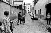 Street scene Julio Le Parc with young family, Paris, France, 1969 - Henri Du Chattillon - 1960s,1969,adult,adults,artist,artists,baguette,boy,boys,bread,child,CHILDHOOD,children,Citroen,cobbled street,DAD,DADDIES,DADDY,DADS,eu,Europe,european,europeans,eurozone,families,family,father,FATHE