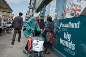 Elderly shoppers chat outside a Poundland store, Kilburn, London. - Philip Wolmuth - 2010s,2016,adult,adults,age,ageing population,BAME,BAMEs,black,BME,bmes,bought,buy,buyer,buyers,buying,cities,City,commodities,commodity,communicating,communication,consumer,consumers,conversation,con