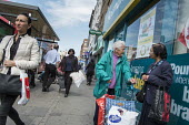 Elderly shoppers chat outside a Poundland store, Kilburn, London. - Philip Wolmuth - 27-05-2016